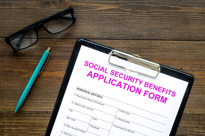 Social security benefits. Application form near pen and glasses on dark wooden background top view copy space
